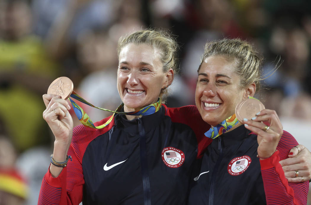 In this Aug. 18, 2016, file photo, United States' Kerri Walsh Jennings, left, and April Ross celebrate their bronze medals in the women's beach volleyball competition at the 2016 Summer Olympics i ...