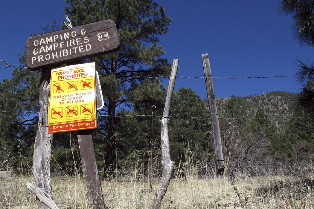 A sign posted at a trail leading into the national forest in Flagstaff, Ariz., warns of extreme fire danger in May. Firefighters are working north of the Grand Canyon to control a wildfire that is ...