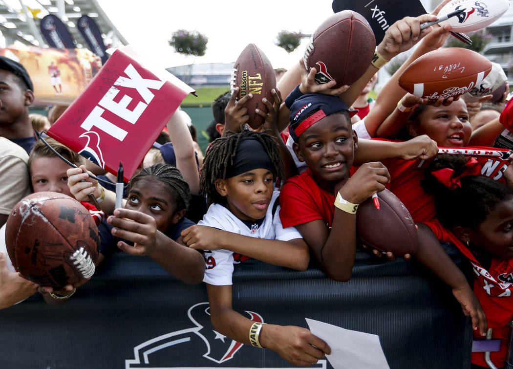 Houston Texans fans wait along a fence line for players to sign autographs during training camp at the Methodist Training Center on Monday, Aug. 13, 2018, in Houston. ( Brett Coomer/Houston Chroni ...