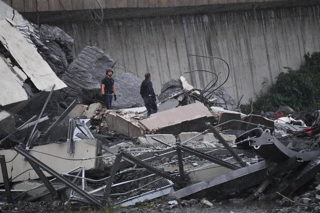 Rescuers work among the rubble of the Morandi highway bridge that collapsed in Genoa, northern Italy, Tuesday, Aug. 14, 2018. A large section of the bridge collapsed over an industrial area in the ...