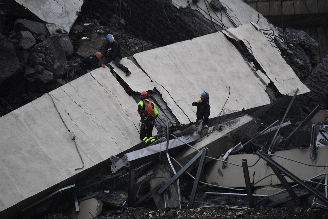 Rescues work among the debris of the collapsed Morandi highway bridge in Genoa, Tuesday, Aug. 14, 2018. Italian authorities say that about 10 vehicles were involved when the raised highway collaps ...