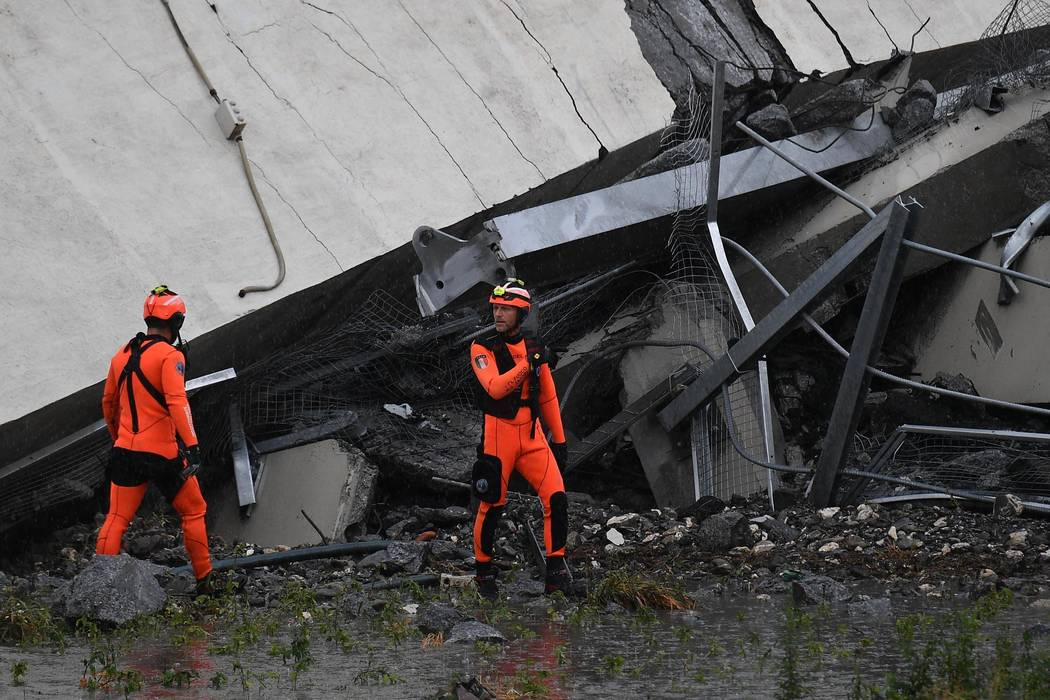 Rescuers among the rubble of the Morandi highway bridge that collapsed in Genoa, northern Italy, Tuesday, Aug. 14, 2018. A large section of the bridge collapsed over an industrial area in the Ital ...