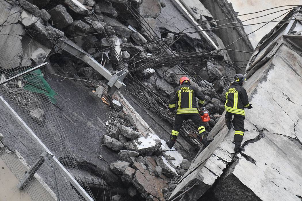 Rescues work among the rubble of the collapsed Morandi highway bridge in Genoa, northern Italy, Tuesday, Aug. 14, 2018. A large section of the bridge collapsed over an industrial area in the Itali ...