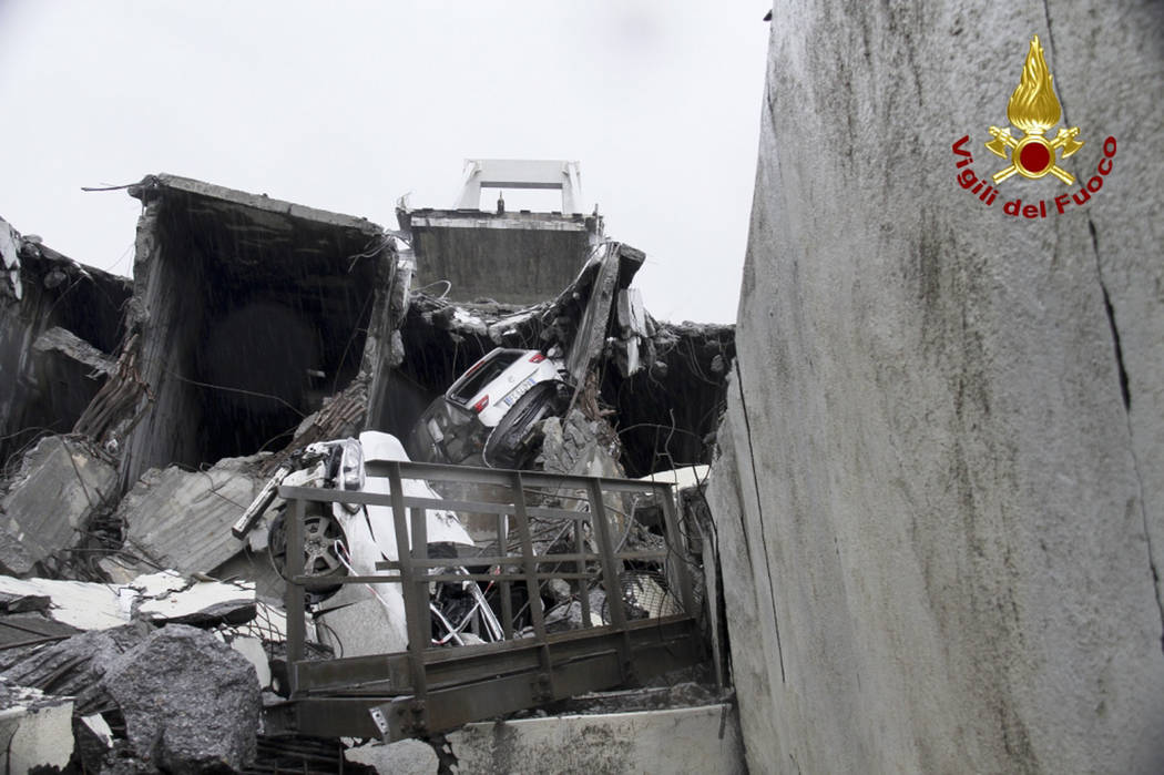 This photo released by the Italian firefighters, cars are seen among the rubble of the collapsed Morandi highway bridge in Genoa, northern Italy, Tuesday, Aug. 14, 2018. A large section of the bri ...