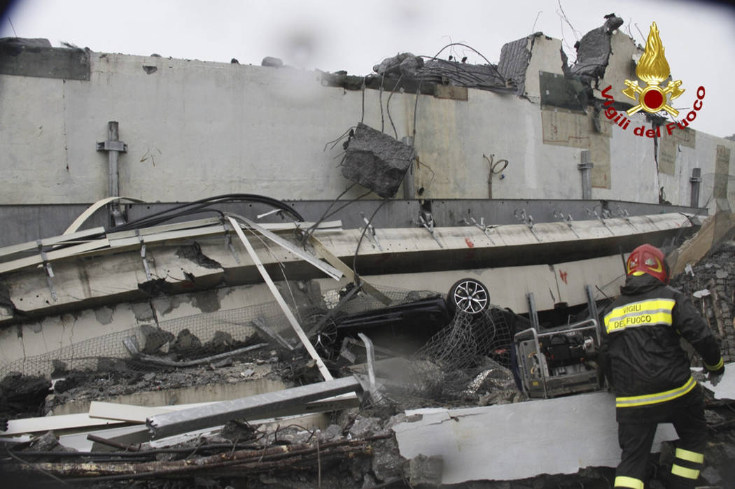 This photo released by the Italian firefighters, rescuers work among the rubble of the collapsed Morandi highway bridge in Genoa, northern Italy, Tuesday, Aug. 14, 2018. A large section of the bri ...