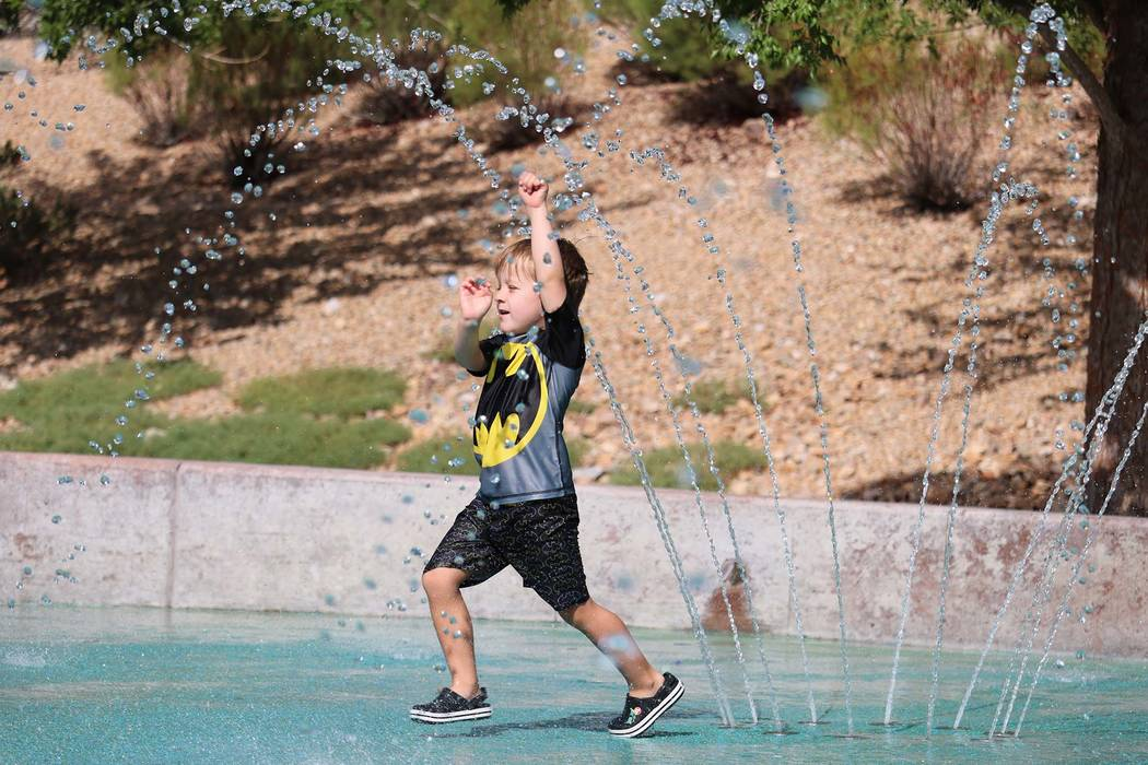 Matthew King, 4, runs through the splash pad at Paseos Park in Summerlin. (Madelyn Reese/Las Vegas Review-Journal)
