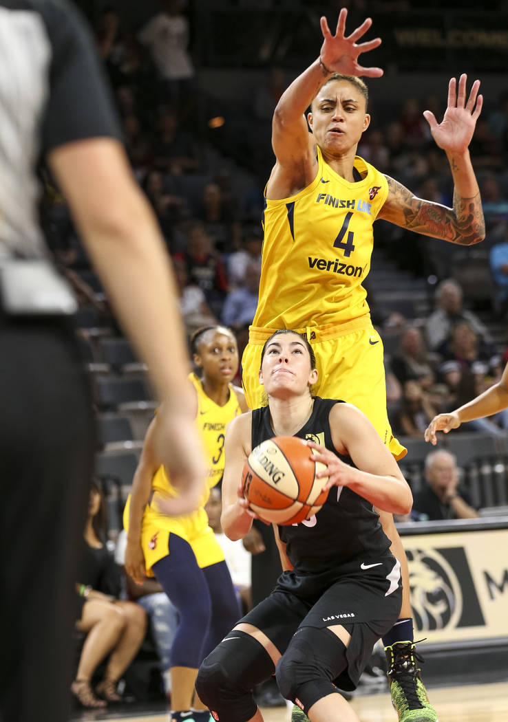 Las Vegas Aces guard Kelsey Plum (10) looks for shot as Indiana Fever forward Candice Dupree (4) goes in for the block during the second half of a WNBA basketball game at the Mandalay Bay Events C ...