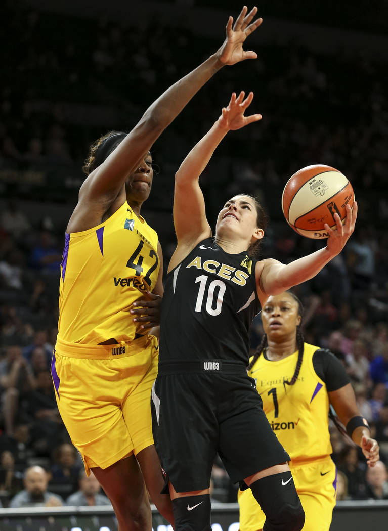 Las Vegas Aces guard Kelsey Plum (10) gets fouled by Los Angeles Sparks center Jantel Lavender (42) as she goes for a shot in the first half of a WNBA basketball game at the Mandalay Bay Events Ce ...