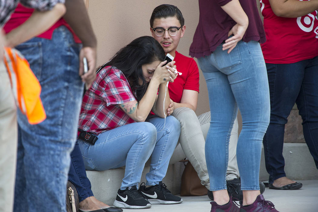 Unidentified Target department store employees comfort each other as Las Vegas police investigate an officer-involved shooting at a shopping complex near Blue Diamond Road and Arville Street in La ...