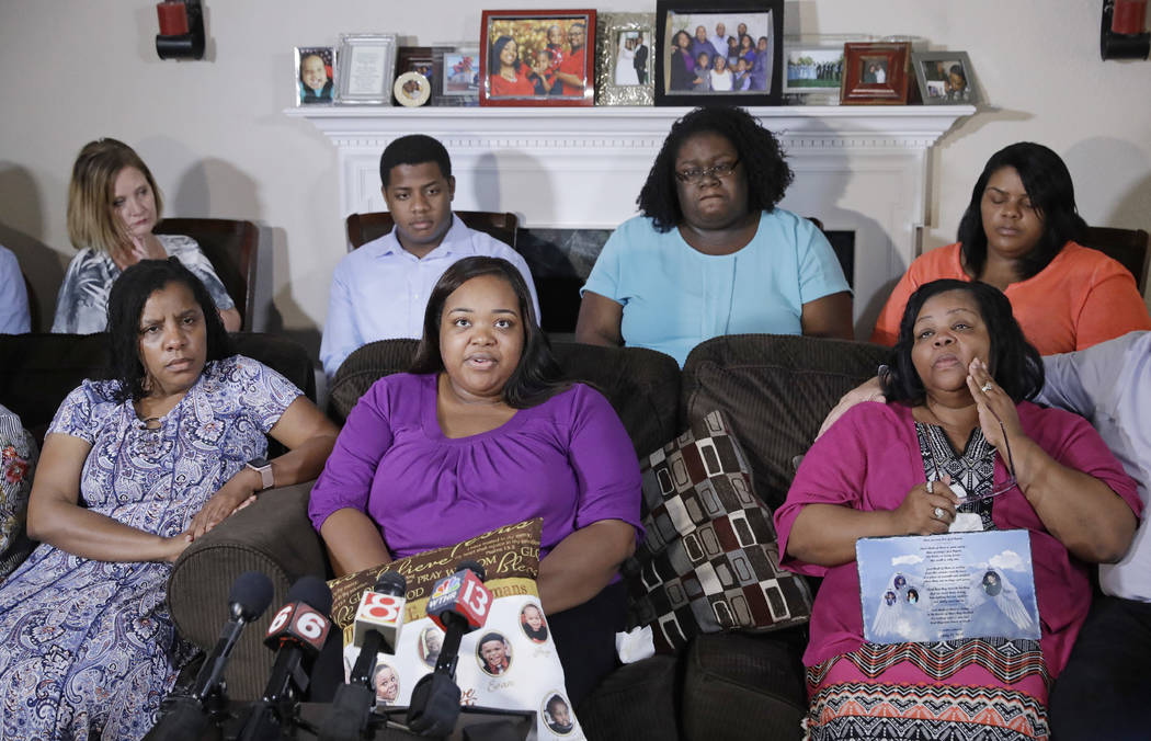 Tia Coleman, middle seated, speaks as she is surrounded by family members during a news conference at her home, Tuesday, Aug. 14, 2018, Indianapolis. Seventeen people died when the boat sank durin ...