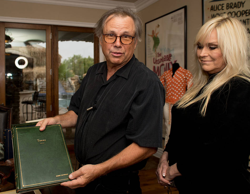 "Todd Fisher holds a bound screenplay script of ""Tammy,"" which is part of his collection of memorabilia from his mother, Debbie Reynold's career. Wife, Catherine Hickland, looks on. (Tonya Harvey R ..."