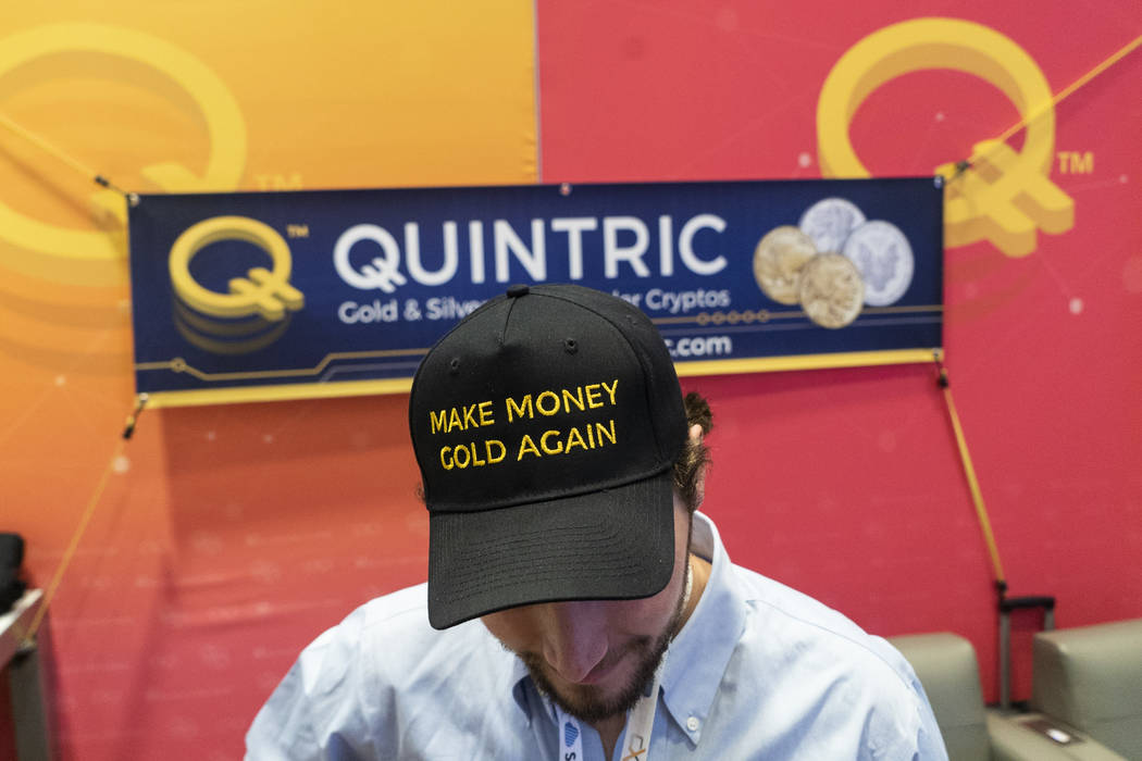 Teddy Thompson,spokesperson for cryptocurrency company Quintric, shows off his hat at his booth at ChainXChange at Mandalay Bay Convention Center in Las Vegas, Tuesday, Aug. 14, 2018. ...