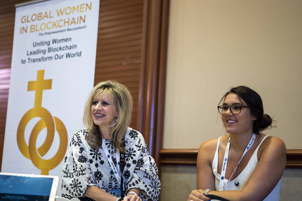 Diana Lange, member, left, and Lisa Ellis, director of public relations for Global Women in Blockchain, speak with attendees at ChainXChange at Mandalay Bay Convention Center in Las Vegas, Tuesday ...