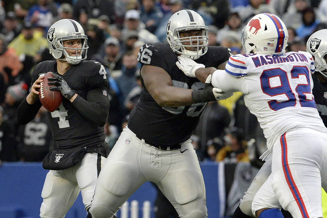 Oakland Raiders quarterback Derek Carr (4) drops back in the pocket as guard Gabe Jackson (66) blocks Buffalo Bills defensive tackle Adolphus Washington (92) during the second half of an NFL footb ...