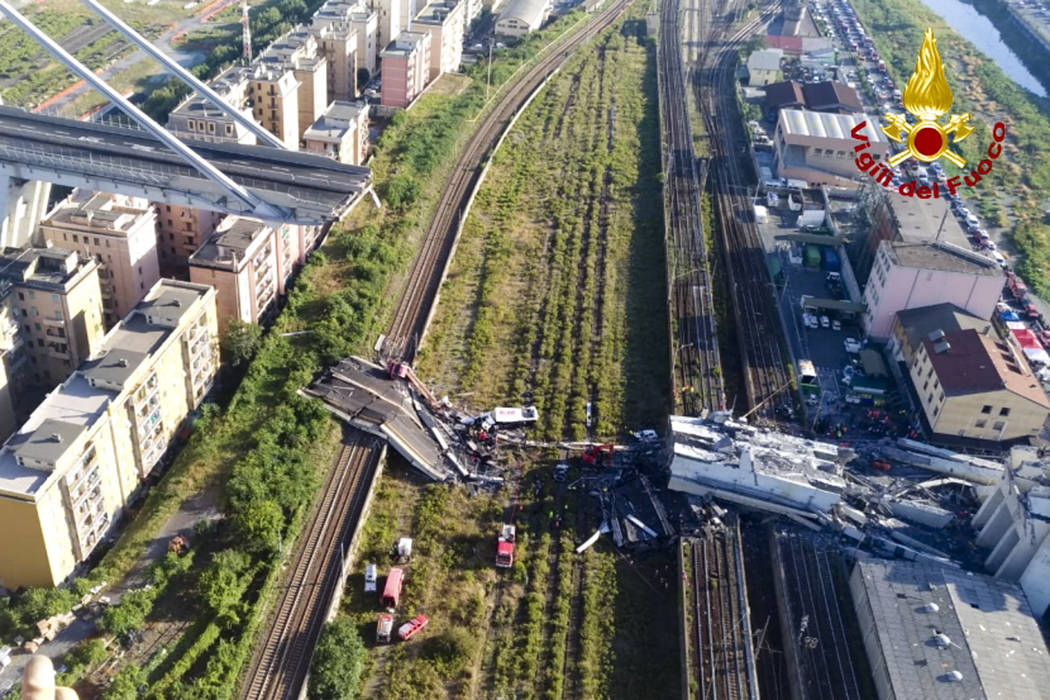 In this photo released by the Italian firefighters, rescue teams work among the rubble of the collapsed Morando highway bridge in Genoa, northern Italy, Tuesday, Aug. 14, 2018. A bridge on a main ...
