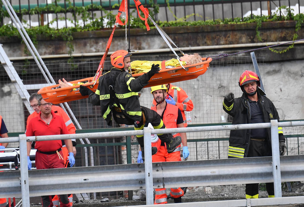 Rescuers recover an injured person after the Morandi highway bridge collapsed in Genoa, northern Italy, Tuesday, Aug. 14, 2018. A large section of the bridge collapsed over an industrial area in t ...
