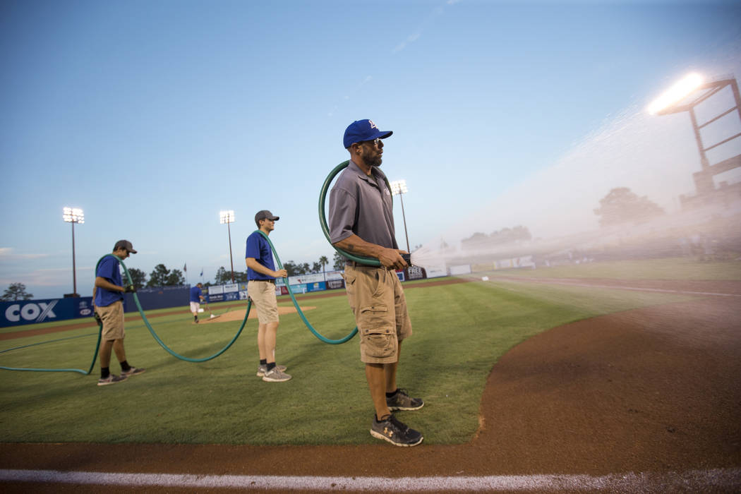 Collin Doebler, right, grounds manager for Cashman Field, and members of his crew prepare the infield before a Las Vegas 51s baseball game at Cashman Field in Las Vegas on Sunday, Aug. 12, 2018. R ...