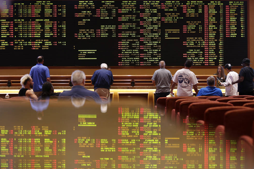 People line up to place bets in the sports book at the South Point hotel-casino, Monday, May 14, 2018, in Las Vegas. (AP Photo/John Locher)