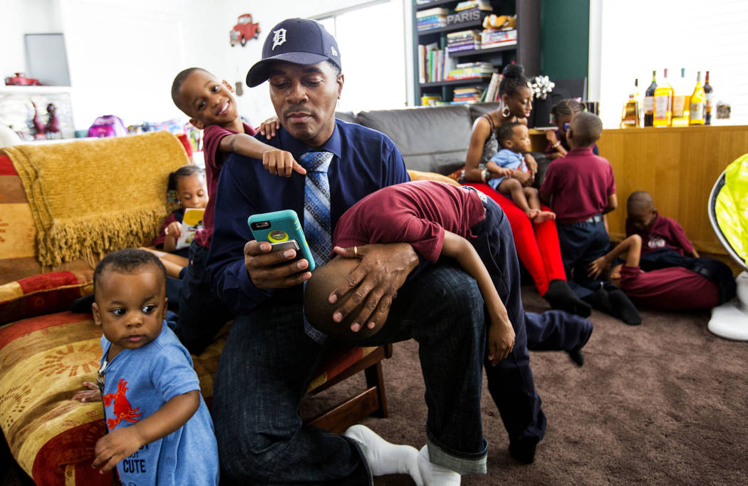 Deon Derrico checks his phone while sitting with his children, from left, Dior, 1, Deniko, 4, and Denver, 6, at his home in North Las Vegas on Wednesday, Aug. 15, 2018, as his wife, Karen Evonne D ...