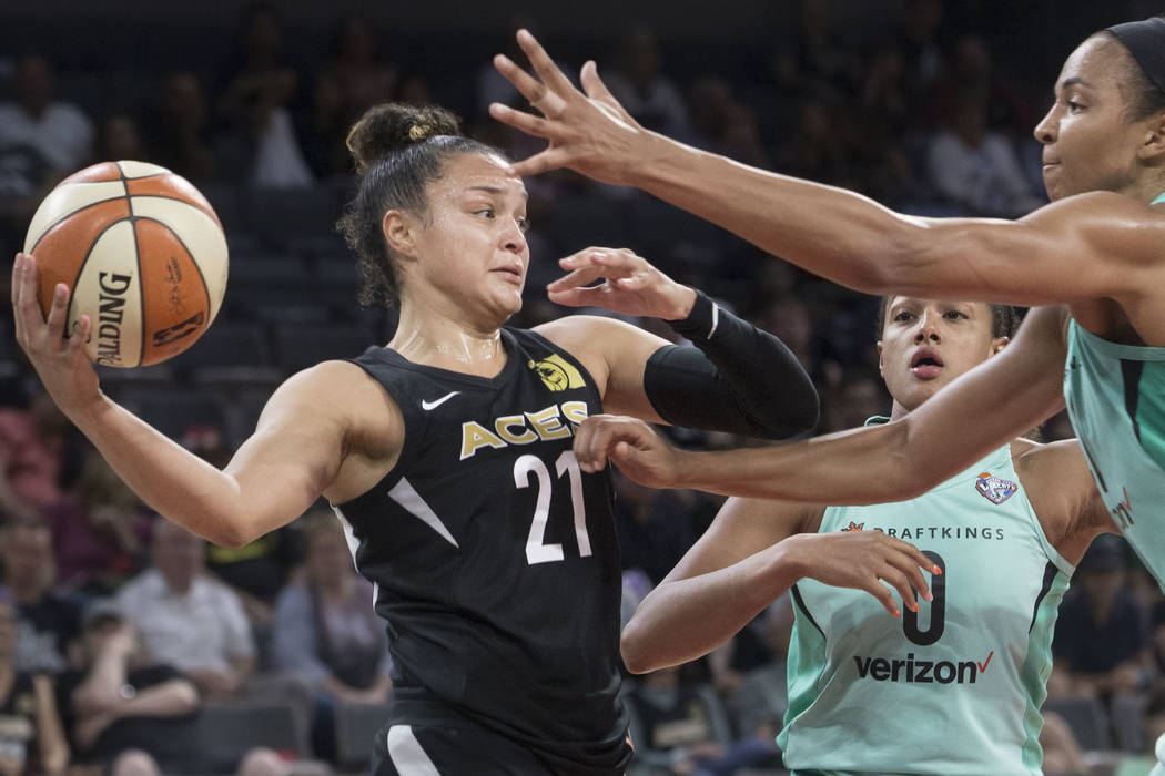 Aces guard Kayla McBride (21) makes a baseline pass around New York Liberty defenders Marissa Coleman (0) and Kiah Stokes (41) in the fourth quarter on Wednesday, Aug. 15, 2018, at the Mandalay Ba ...