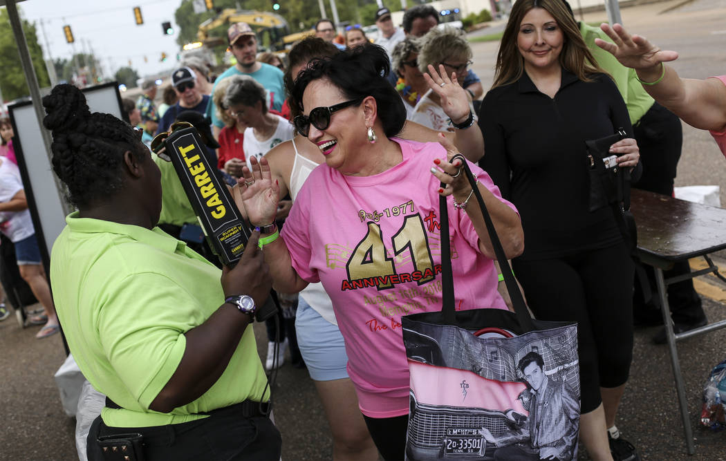 "Elvis Presley fan Dianne Jeddor, center, of Toronto, Canada, makes her way to a candlelight vigil during ""Elvis Week"" that marks the 41st anniversary of Presley's Aug. 16 death, on Wedne ..."
