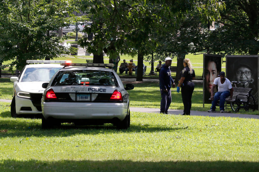 A police officer speaks to a man walking on New Haven Green, Wednesday, Aug. 15, 2018, in New Haven, Conn. A city official said more than 45 people fell ill from suspected drug overdoses on the gr ...