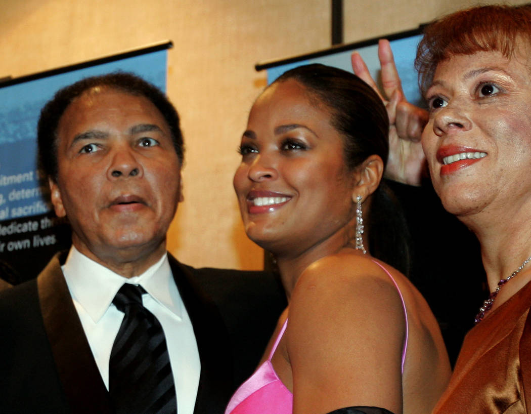 FILE - In this Feb. 26, 2005, file photo, former heavyweight boxing champion Muhammad Ali, left, jokingly holds up two fingers behind the head of his daughter, Laila Ali, as they and his wife, Lon ...
