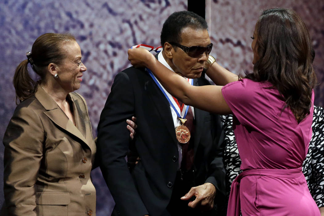 Retired boxing champion Muhammad Ali, center, receives the Liberty Medal from his daughter Laila Ali with his wife Lonnie Ali at his left during a ceremony at the National Constitution Center, Thu ...