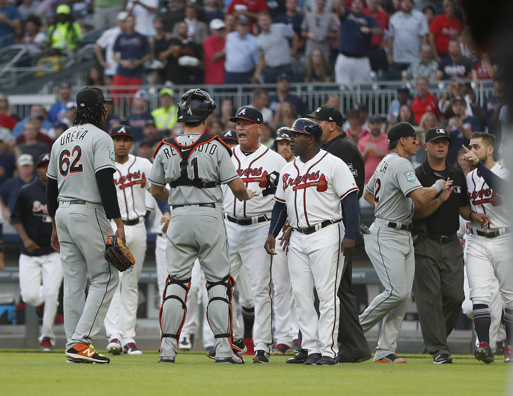 Miami Marlins catcher J.T. Realmuto (11) stands between pitcher Jose Urena (62) and Atlanta Braves manager Brian Snitker (43) as the dugouts empty after Urena hit Braves' Ronald Acuna Jr. with a p ...