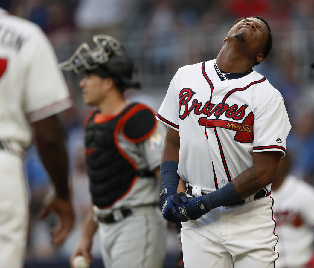 Atlanta Braves' Ronald Acuna Jr., right, reacts after being hit by a pitch from Miami Marlins'Jose Urena during the first inning of a baseball game Wednesday , Aug. 15, 2018 in Atlanta. Both dugou ...