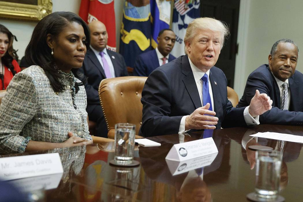 President Donald Trump, center, is flanked by White House staffer Omarosa Manigault Newman, left, and then-Housing and Urban Development Secretary-designate Ben Carson during a meeting at the Whi ...