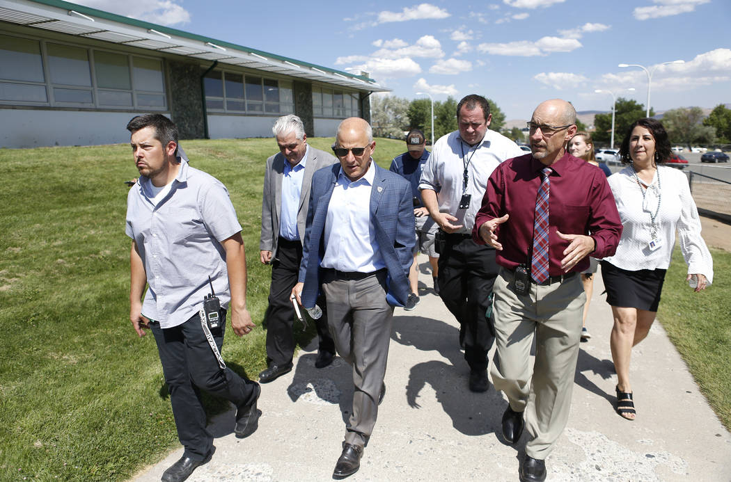 Officials from Hug High School in Reno, Nev., give Raiders president Marc Badain, center, a tour of the campus on Thursday, Aug. 16, 2018. The Raiders are considering several potential training ca ...