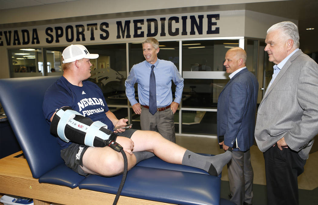 University of Nevada, Reno Athletic Director Doug Knuth, left, Raiders president Marc Badain and Democratic governor candidate Steve Sisolak talk with student athlete Sean Krepsz during a tour of ...