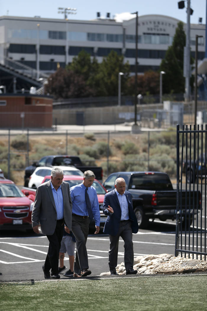 From left, Democratic governor candidate Steve Sisolak, University of Nevada, Reno Athletic Director Doug Knuth, center, and Raiders president Marc Badain tour the campus in Reno, Nev., on Thursda ...