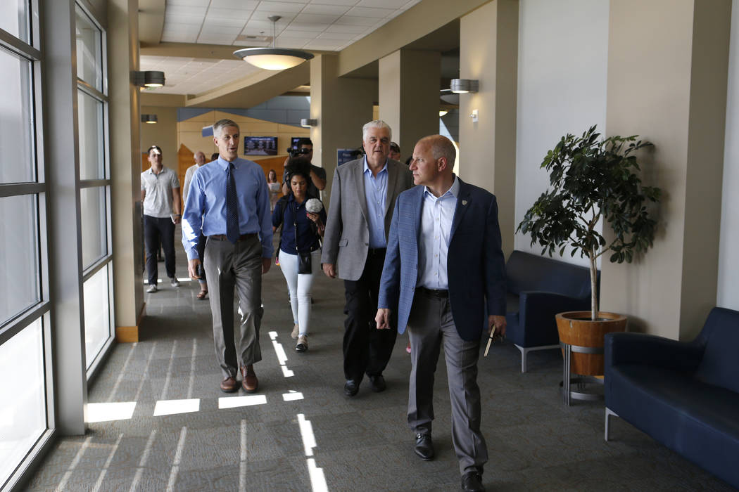 From left, University of Nevada, Reno Athletic Director Doug Knuth, Democratic governor candidate Steve Sisolak, and Raiders president Marc Badain tour the campus in Reno, Nev., on Thursday, Aug. ...