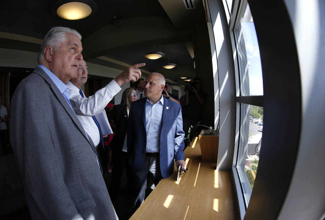 From left, Democratic governor candidate Steve Sisolak, University of Nevada, Reno President Marc Johnson and Raiders president Marc Badain tour the campus in Reno, Nev., on Thursday, Aug. 16, 201 ...