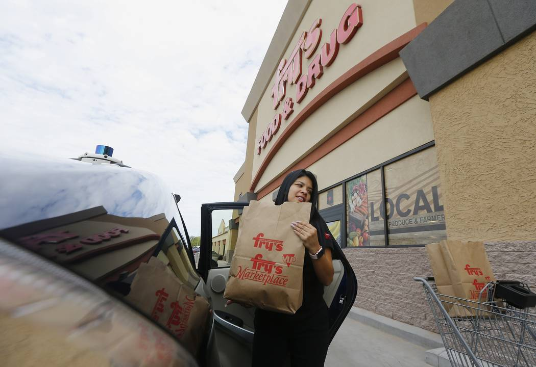 Fry's customer service representative Yuri Alvarado puts groceries into the self-driving Nuro vehicle parked outside a Fry's supermarket, which is owned by Kroger, as part of a pilot program for g ...