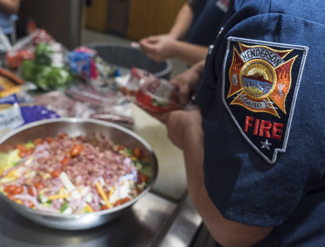 Henderson Firefighters prepare a meal at Fire Station 82 in Henderson, Wednesday, Aug. 8, 2018. Henderson Firefighters Benevolent Association donated 10 grills for a total of $9,820 to the Henders ...