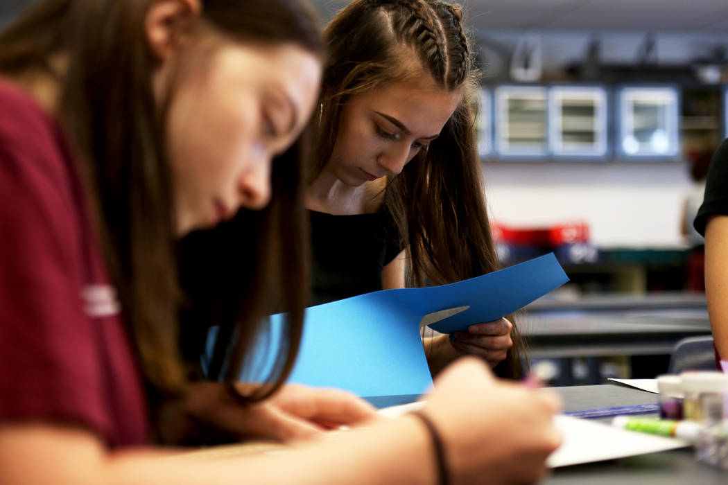 Autumn Berner, 15, left, and Abbey Mashore, 15, create social media logos on paper for the bulletin board at school to get the word out about their robotics team at Las Vegas Academy in Las Vegas, ...