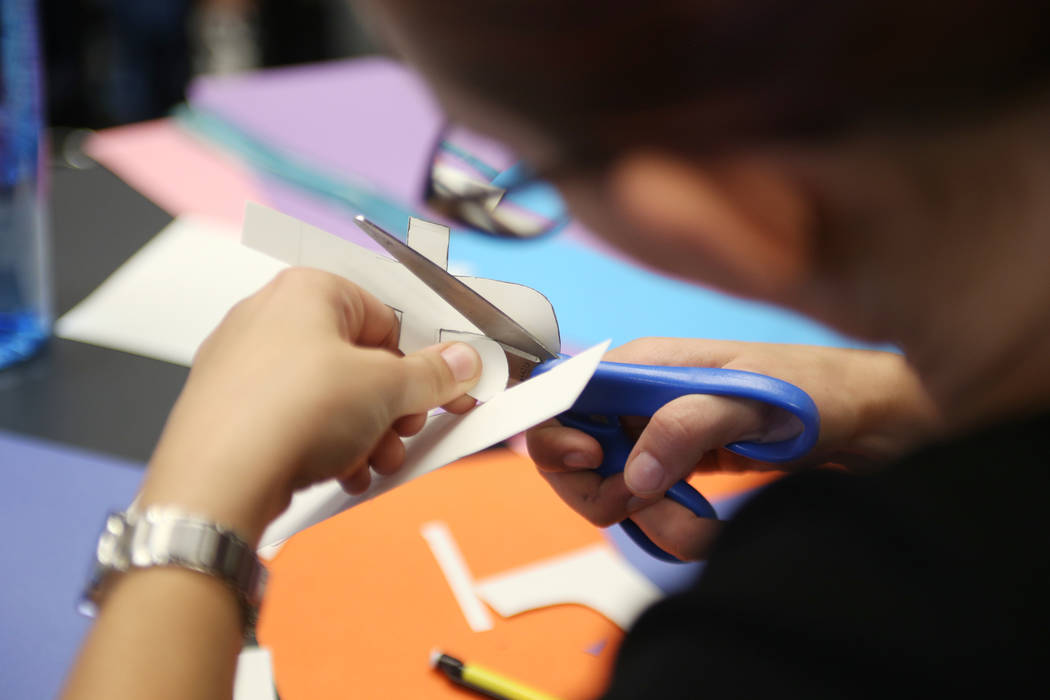 Chloe Dell, 17, creates a social media logo on paper for the bulletin board at school to get the word out about their robotics team at Las Vegas Academy in Las Vegas, Thursday, Aug. 16, 2018. The ...