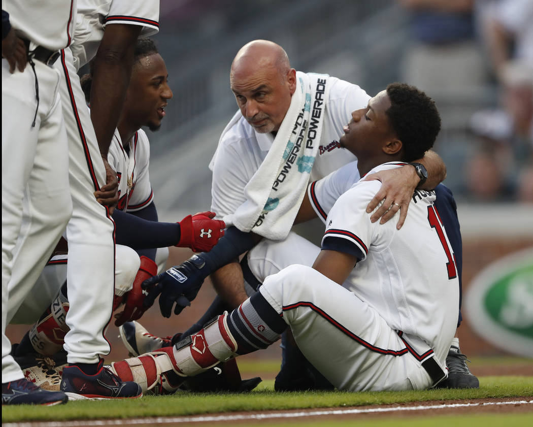 Atlanta Braves' Ronald Acuna Jr. (13) is tended to by a member of the training staff as Ozzie Albies talks to him after Acuna was hit by a pitch from Miami Marlins starting pitcher Jose Urena duri ...
