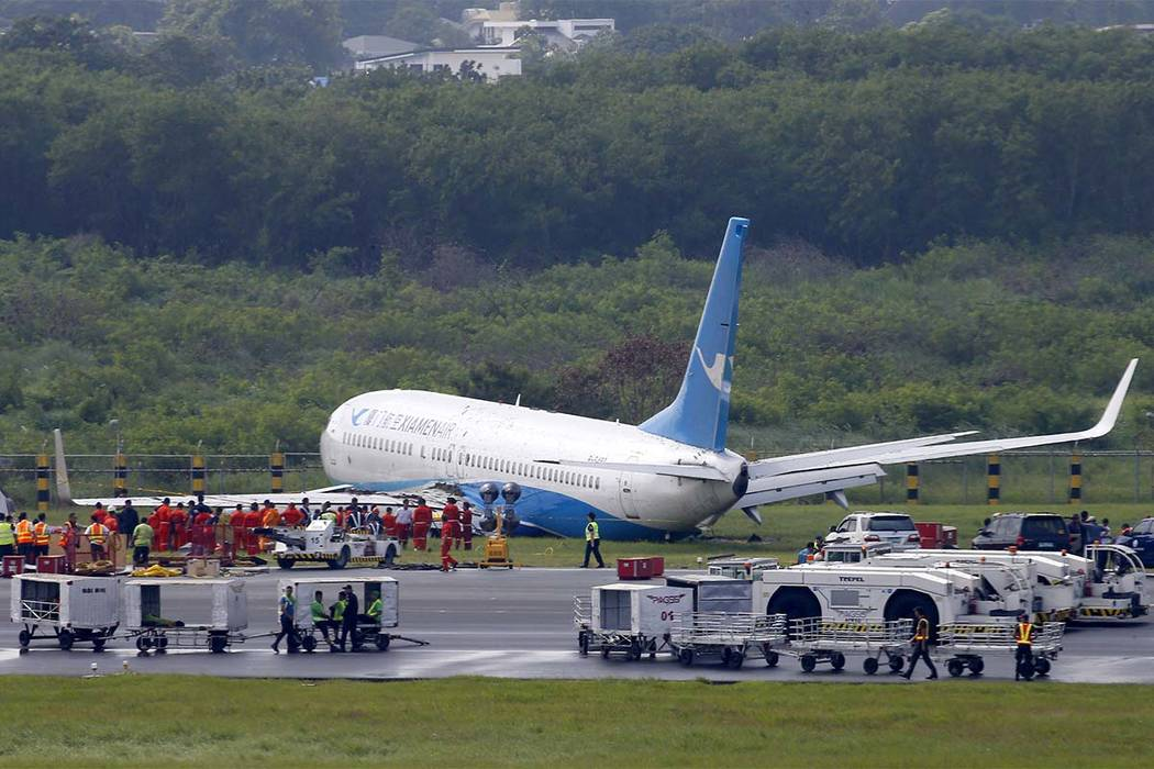 A Boeing passenger plane from China, a Xiamen Air, sits on the grassy portion of the runway of the Ninoy Aquino International Airport after it skidded off the runway while landing Friday, Aug. 17, ...