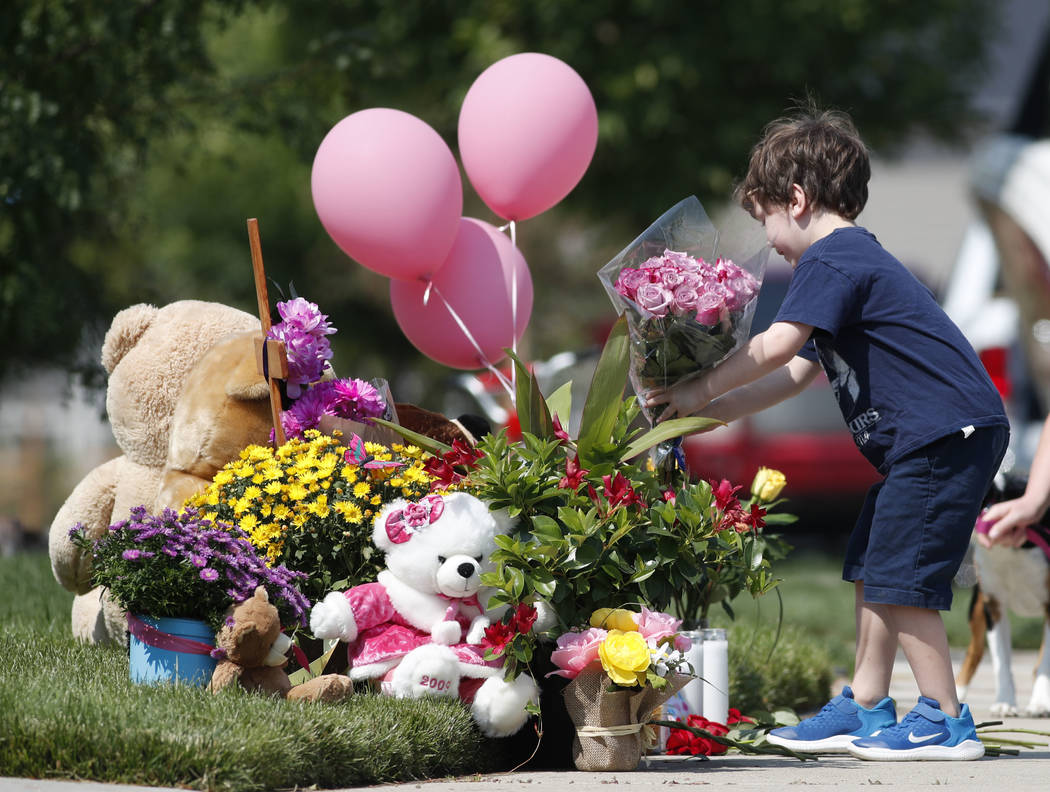 An unidentified young boy places a bouquet of flowers on a pile of tributes outside the home where a pregnant woman and her two daughters lived Thursday, Aug. 16, 2018, in Frederick, Colo. The wom ...