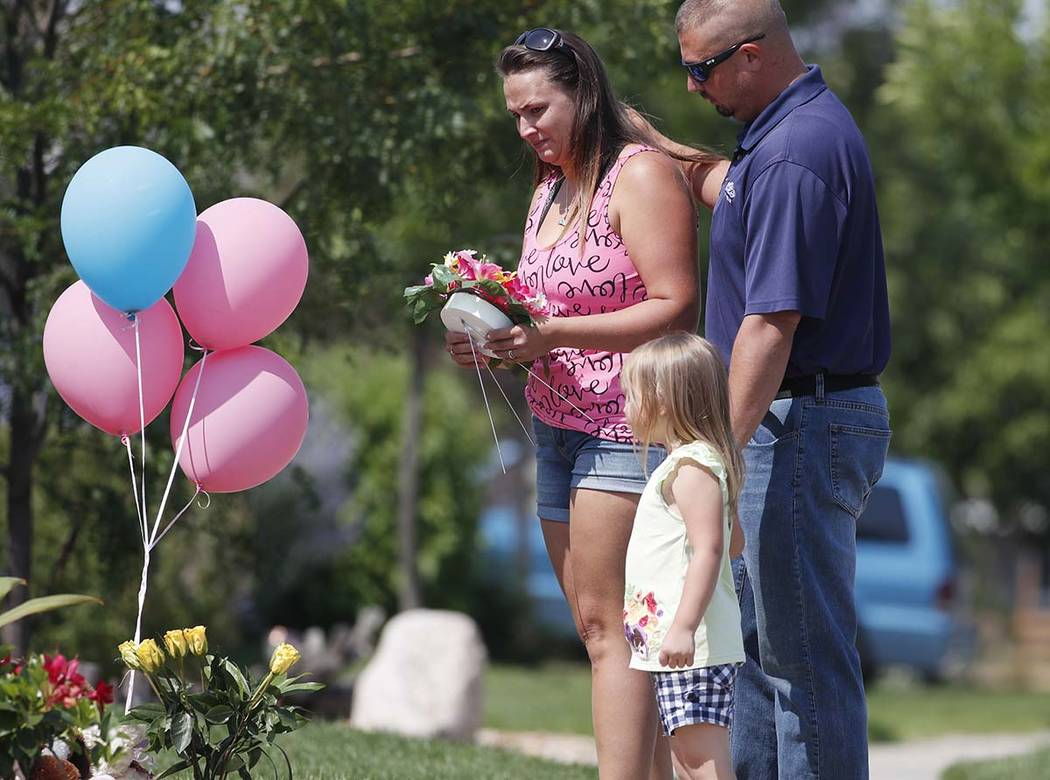 Ashley Bell, left, is consoled by her husband, Steven, and 4-year-old daughter Liberty as the woman places a tribute outside the home where a pregnant woman and her two daughters lived Thursday, A ...