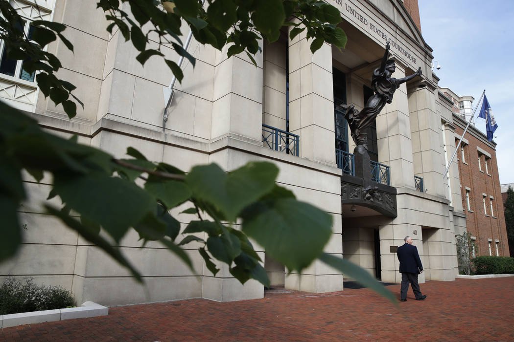 A security guard walks by the front of federal court as jury deliberations begin in the trial of the former Trump campaign chairman, in Alexandria, Va., Thursday, Aug. 16, 2018. (Jacquelyn Martin/AP)