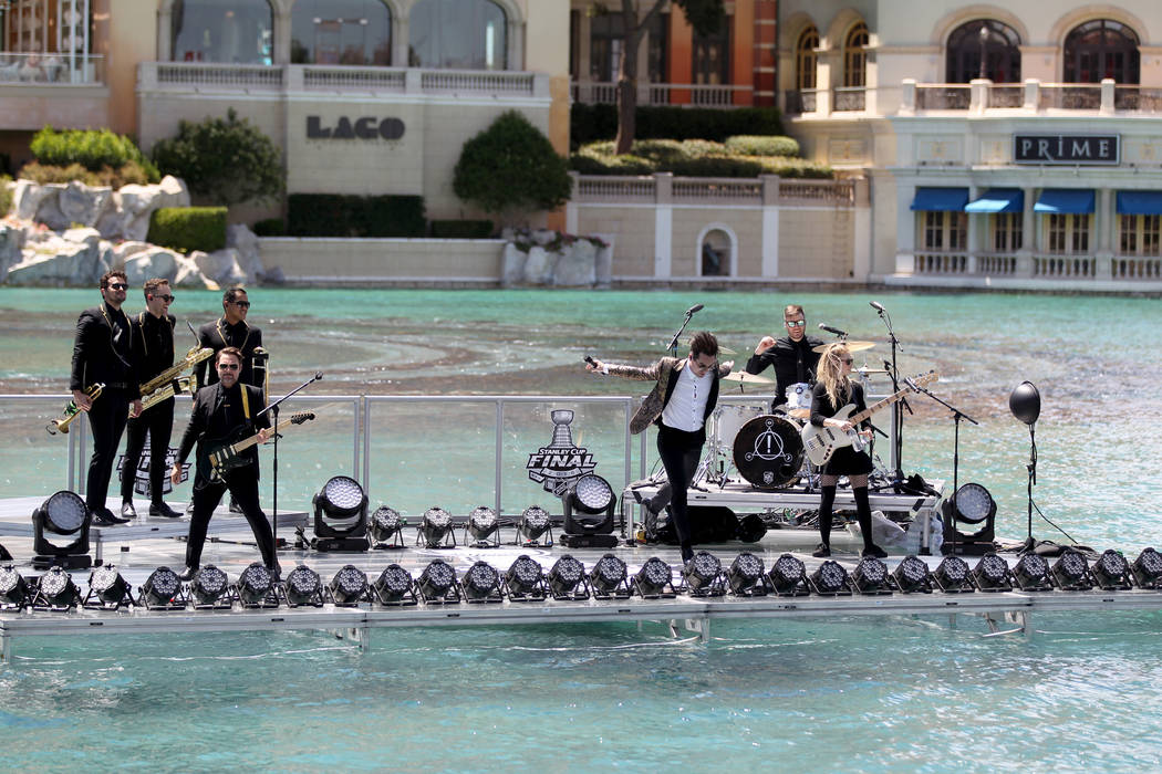 Frontman Brendon Urie, center, of the Las Vegas rock band Panic! at the Disco pretends to dive in the water after performing at the Fountains at Bellagio ahead of the Vegas Golden Knights-Washingt ...