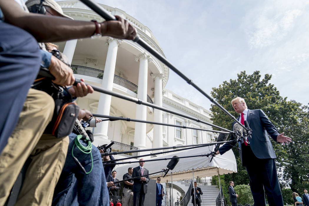 President Donald Trump speaks to members of the media before boarding Marine One on the South Lawn at the White House in Washington, Friday, Aug. 17, 2018, for a short trip to Andrews Air Force Ba ...