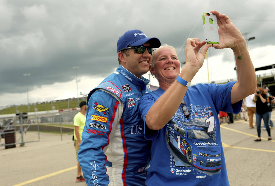Elliott Sadler stops to pose for a selfie with a fan after winning the pole for the NASCAR Xfinity Series auto race, Saturday, July 28, 2018, at Iowa Speedway in Newton, Iowa. (AP Photo/Justin Hay ...