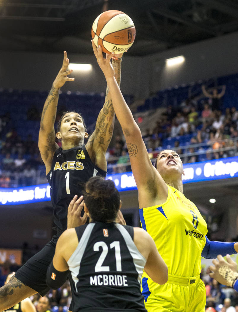 Dallas Wings center Liz Cambage (8) attempts to shoot a basket while Las Vegas forward Tamera Young (1) and guard Kayla McBride (21) attempt to block during the game against the Las Vegas Aces at ...