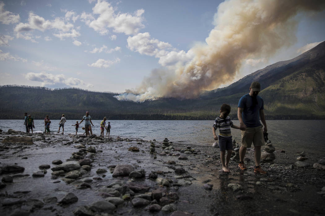 People walk along the shore near Lake McDonald Lodge as the Howe Ridge Fire burns in Glacier National Park, Mont., on Aug. 12, 2018. (National Park Service via AP)